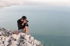 Photographer sitting stone cliff above lake sea. Royalty Free Stock Photo