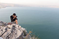 Photographer sitting stone cliff above lake sea. Royalty Free Stock Photos