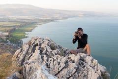 Photographer sitting stone cliff above lake sea. Royalty Free Stock Photos