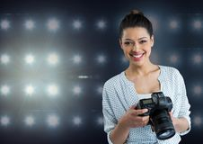 photographer smiling  looking to the photos on camera .stadium lights  background Royalty Free Stock Images