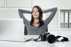 Photographer smiling in satisfaction at her images Royalty Free Stock Photography
