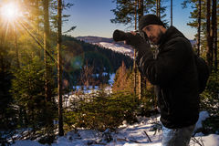Photographer in snowy coniferous forest at sunset stock photo