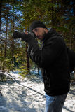 Photographer in snowy coniferous forest stock image