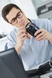 Photographer soldering wireless flash trigger at workplace Royalty Free Stock Images