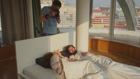 Photographer takes pictures on the bed. The photographer is standing on top, taking pictures of models that lie on the bed in apartments stock video