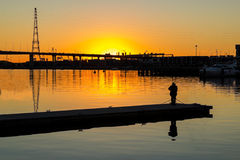 A photographer stands on a pier to take photos. Of an orange sunset Royalty Free Stock Images