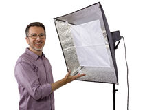Photographer with Studio Lighting. Male photographer showing or demonstrating how to use a soft box studio light for photography on a white background stock photo