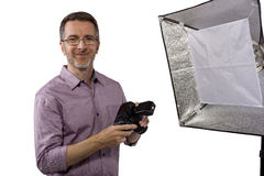 Photographer with Studio Lighting. Male photographer showing or demonstrating how to use a soft box studio light for photography on a white background stock photography