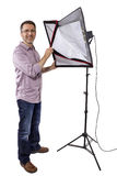 Photographer with Studio Lighting. Male photographer showing or demonstrating how to use a soft box studio light for photography on a white background royalty free stock photo