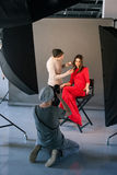 Photographer and stylist work in studio. Man taking shot of female model, visagist doing makeup. Creative team make commercials. Photo school, lookbook Royalty Free Stock Image