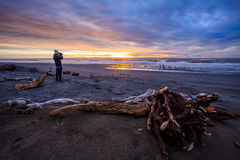 Photographer and sun set on black beach hokitika south island ne. W zealand Royalty Free Stock Photos