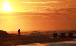 Photographer at sunrise photographing the ocean. Photographer on the beach at sunrise taking pictures of the ocean as a hurricane hermine hovers  off of the Stock Images