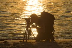 Photographer in sunset. Silhouette of a photographer in a sunset. Water in the background Royalty Free Stock Photo