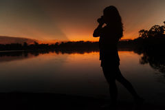 Photographer at sunset. Silhouette of a female photographer at sunset Stock Photo