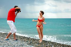 The photographer take pictures a girl. The photographer take pictures a model in red bikini on a beach Royalty Free Stock Images