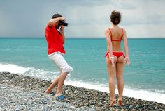 The photographer take pictures a girl. The photographer take pictures a model in red bikini on a beach Royalty Free Stock Image