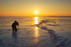 Photographer take pictures on the ice at sunset Stock Photos