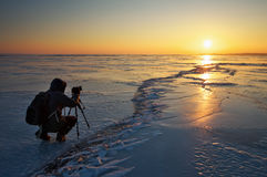 Photographer take pictures on the ice at sunset Royalty Free Stock Photos