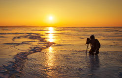 Photographer take pictures on the ice at sunset Stock Photo