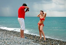 The photographer take pictures a model. In bikini on a beach Stock Photo