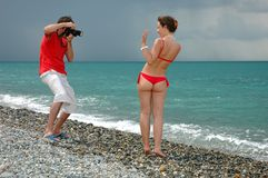 Photographer take pictures a model in bikini. The photographer take pictures a model on a beach Royalty Free Stock Photos