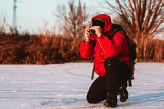 Photographer take pictures on the river bank in winter Royalty Free Stock Image