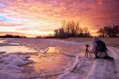 Photographer take pictures on the river bank in winter. royalty free stock photos