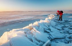 Photographer take pictures on the river coast in winter. Time stock image