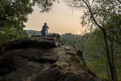 Photographer take sunrise shot at summit of hill Stock Photo