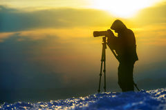 Photographer takes a landscape picture. Photographer  silhouette against the multicolored sky. Shine snow is in  the foreground. The story about landscape photo Stock Photography