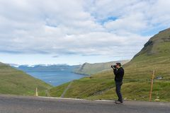 Photographer takes a photo of kaldbaksfjordur fiord from a butte Royalty Free Stock Photo