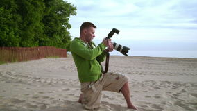 Photographer takes photo on sea beach. Photographer working stock footage