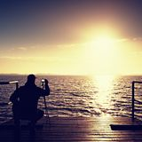 Photographer takes photos with mirror camera and tripod at end of pier board. Royalty Free Stock Photo