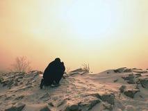 Man  takes picture of freeze autumnal daybreak, rocks with powder snow. Photographer takes picture of freeze autumnal daybreak, rocks covered with fresh powder Stock Photo