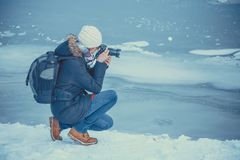 Photographer takes picture of frozen lake. Portrait of female photographer shooting winter landscape next to the frozen lake Stock Image