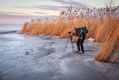 Photographer takes a picture on a frozen lake Royalty Free Stock Photo