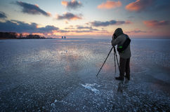 Photographer takes a picture of sunset on a frozen river Royalty Free Stock Photography