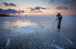 Photographer takes a picture of sunset on a frozen river Stock Photography