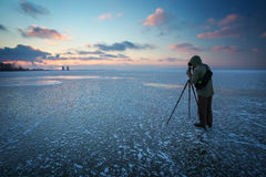Photographer takes a picture of sunset on a frozen river Royalty Free Stock Photos