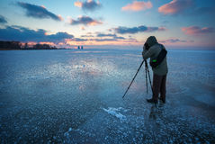 Photographer takes a picture of sunset on a frozen river Stock Images
