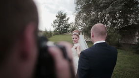 A photographer takes pictures of a beautiful young couple on their wedding day stock footage