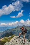 Photographer takes pictures in the mountains. Photographer taking pictures on the rocks in the Alps - Austria Stock Image