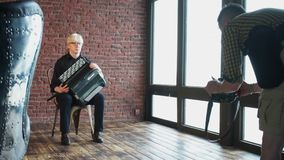 A photographer takes pictures of a musician with an accordion. Photographer takes a musician with an accordion in the studio stock footage