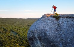 The photographer takes pictures of landscapes. The photographer takes pictures of the scenery on the rock in the evening Royalty Free Stock Photos