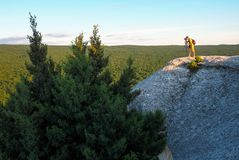 The photographer takes pictures of the scenery on the rock. In the evening Stock Photo