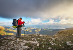 Photographer takes pictures on top of the mountain in autumn. Royalty Free Stock Photo