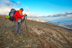 Photographer takes pictures on top of the mountain in autumn. Royalty Free Stock Photos
