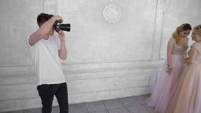 Photographer takes pictures of two beautiful girls in a white interior studio. The photographer takes pictures of two beautiful 20s girls in a white interior stock video footage