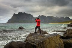 Photographer takes pictures at Uttakleiv beach on Lofoten island royalty free stock image