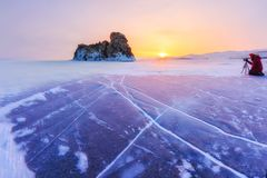 Photographer takes pictures winter ogoy island at sunrise in the ice of Lake Baikal, Russia.